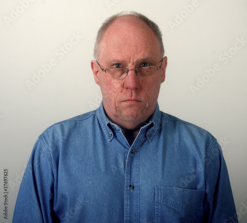 f6b47c6ef764 Older Man in Blue Denim Shirt and Glasses Looking Glum - Buy this ...