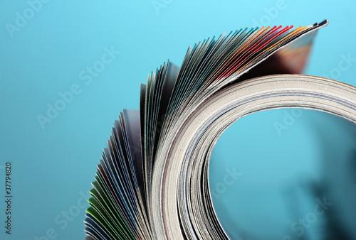 Valokuva  Rolled up magazines on blue background