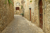 narrow  paved street and stone walls in italian village, Montefi