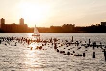 A Sailing Boat Crosses Hudson River At Sunset