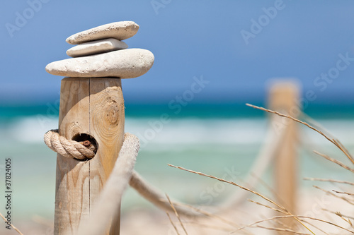 Foto op Plexiglas Stenen in het Zand Stones balanced on wooden banister near the beach.