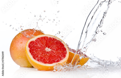 Foto op Canvas Opspattend water Grapefruit slice in water splash, isolated on white background