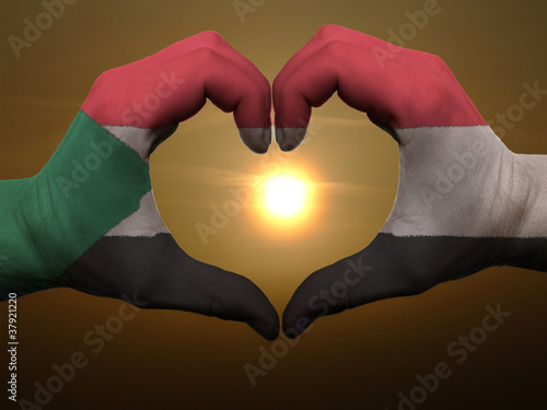 Poster Algérie Heart and love gesture by hands colored in sudan flag during bea