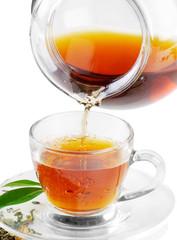 Fototapeta Do herbaciarni Tea being poured into tea cup isolated on a white background