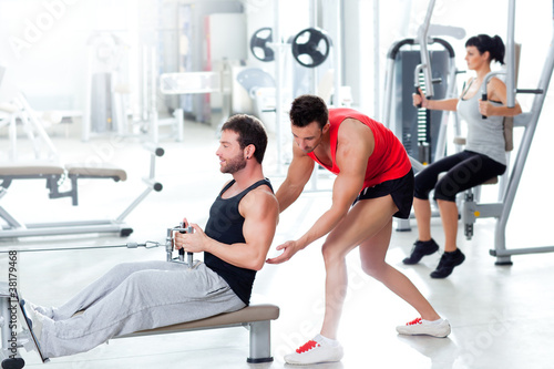 Spoed Foto op Canvas Fitness gym man with personal trainer and fitness woman