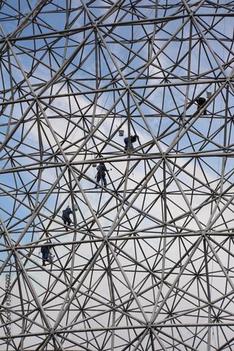 Fotografia  Climbers on a metallic net structure painting the sky.