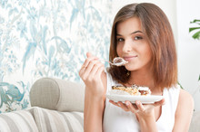 Smiling Brunette Woman Eating Some Cake In The Living Room In He
