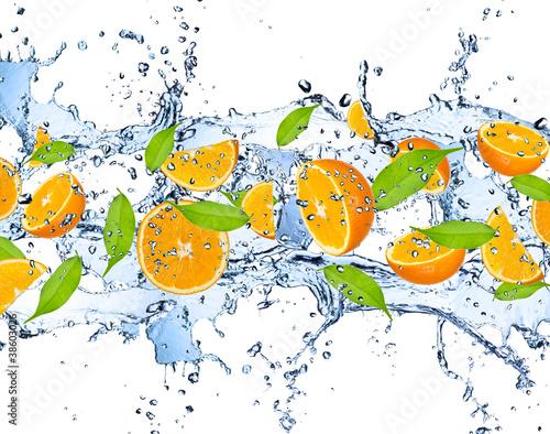 swieze-polowki-pomaranczy-w-strumieniu-wody-na-bialym-tle