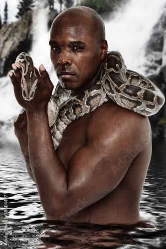 Photo  Attractive Fit Black Man with Boa Constrictor Standing in Lake