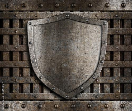 aged metal shield on wooden medieval gates Fototapeta