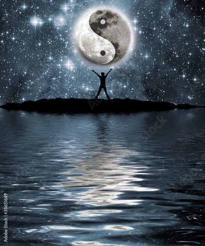 Fotografija  Man in front of moon with the sign of the yin and yang