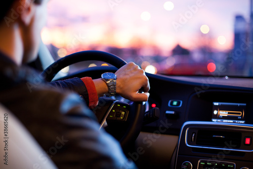 Fototapeta Driving a car at night - young man driving her car
