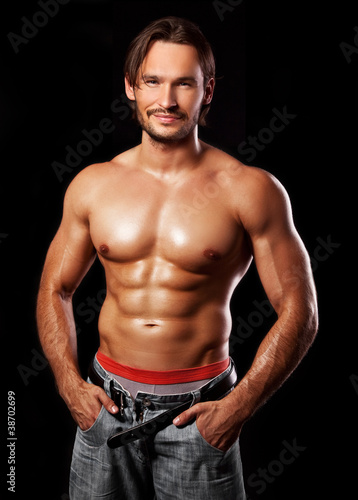 Fototapeta premium handsome powerful muscular man isolated on black