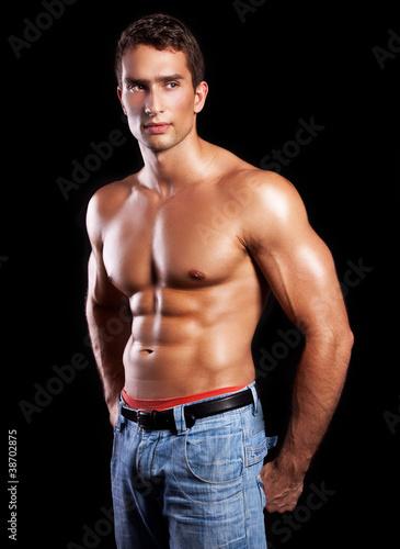 Naklejka premium handsome powerful muscular man isolated on black