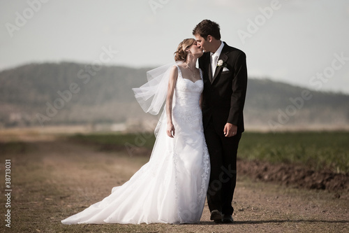 Fotografie, Obraz  Bride and Groom walking down a rural road and kissing