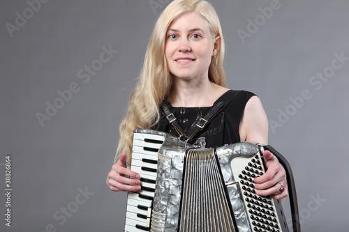 Fényképezés  Beautiful young woman with an accordion.