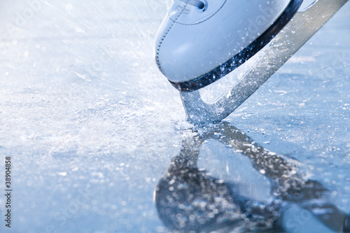 Canvas Print Woman skates braking ice, frazil flying around