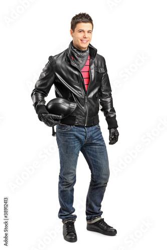 Fotografia Young motorcycler holding a helmet posing