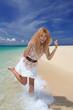 浜辺で波とたわむれる笑顔の女性