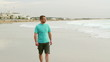 Man walking on beach and looking at the sea
