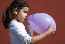 Girl Blowing Up Balloon