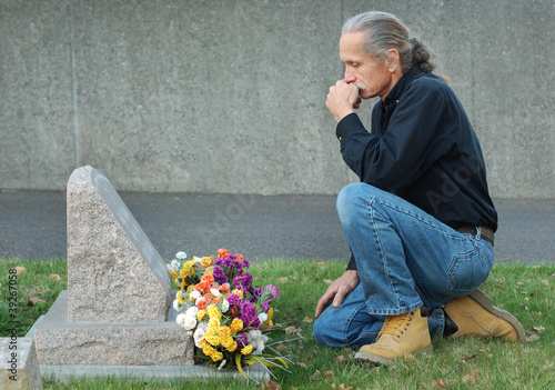 Photo Man sitting at gravesite