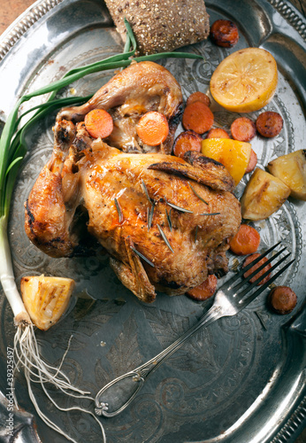 Roasted chicken on old silver plate