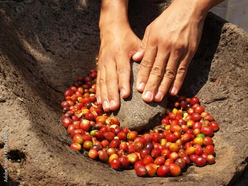 Fotografía Grinding coffee berries in hand mortar
