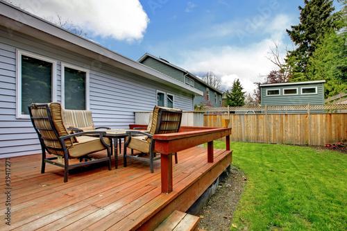 Fototapeta Grey small house with simple deck and outdoor chairs. obraz na płótnie