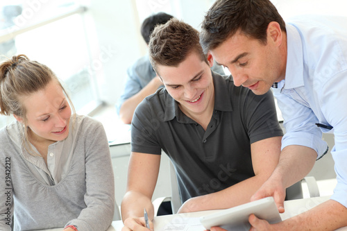 Teacher helping students with assignment Canvas Print