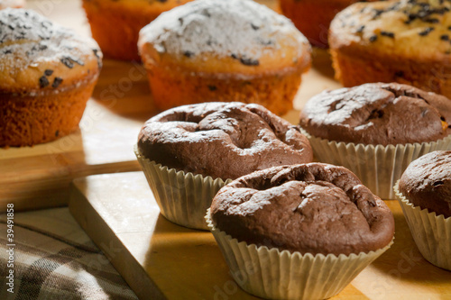 Chocolate and vanilla muffins on wooden board