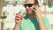 Happy man talking on cellphone and drinking, steadicam shot