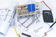 Modellhaus mit Bauplan, Zirkel, Geodreieck und Taschenrechner