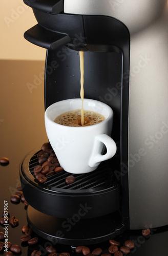 Plakaty o nałogach kawy-espresso-maszynowa-nalewa-kawa-w-filizance-na-brown-tle