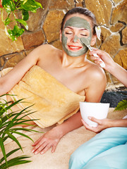 Fototapeta Do Spa Girl having clay body mask apply by beautician.