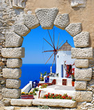 Windmill through an old window in Santorini island, Greece
