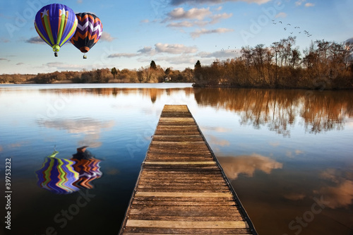 Tuinposter Pier Hot air balloons over sunset lake with jetty