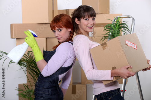 Fotografering  Young women cleaning out their apartment on moving day