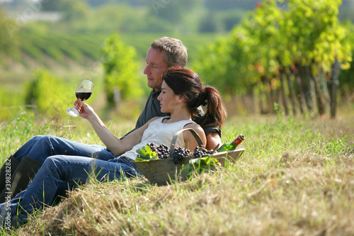 Tuinposter Wijngaard Couple tasting wine at a vineyard