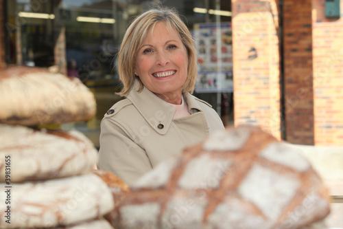 Foto op Plexiglas Bakkerij Woman behind loaves of bread