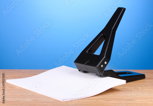 Valokuva  Black office hole punch with paper on blue background