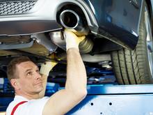 Motor Mechanic Fixing The Exha...