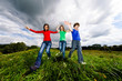 Active family - mother and kids jumping outdoor