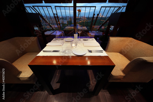 Photo serving at table with tablecloth and seats in empty restaurant