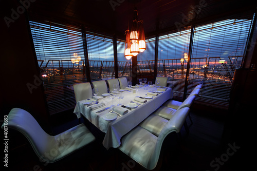Photo table with white tablecloth and serving and chairs in restaurant