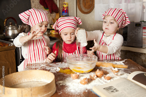Fotografía  Three little chefs enjoying in the kitchen making big mess. Litt