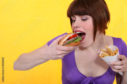 Woman eating hamburger and fries Canvas-taulu