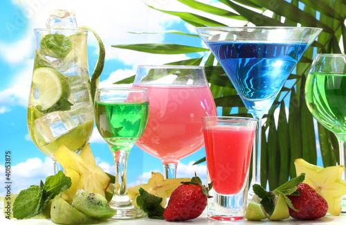 Fototapeta Glasses of cocktails on table on blue sky background