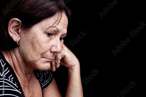 Fotografía  Triste y preocupada mujer mayor aislados en negro