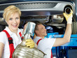 Motor mechanic and apprentice repair the exhaust system of a car